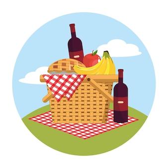 Cesto con bottiglia di vino e frutta nella tovaglia