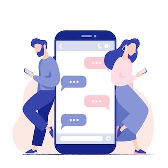 Chat parla di giovani con gli smartphone. uomo e donna in piedi vicino al grande telefono cellulare con fumetti in chat. relazione virtuale, millennial.
