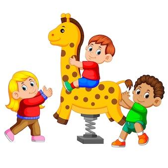 Childrem felice che gioca sulla giraffa del cavaliere della molla