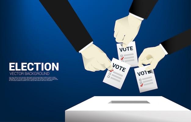 Chiuda sulla mano dell'uomo d'affari che ha messo il loro voto alla scatola di elezione.