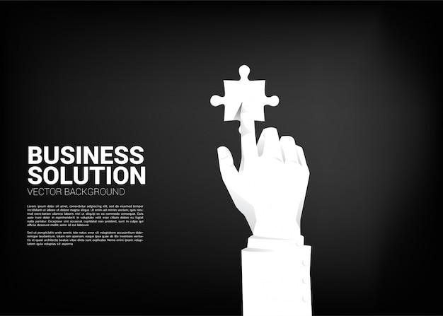 Chiuda sulla parte del puzzle di tocco della mano dell'uomo d'affari.