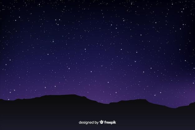 Cielo notturno stellato sfumato con le montagne