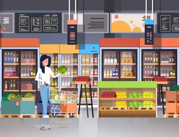 Cliente della donna del supermercato con il carrello del carrello