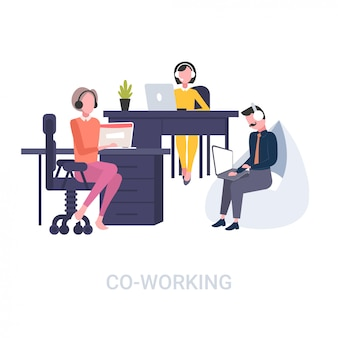 Colleghe in operatori di cuffia avricolare che si siedono al fondo bianco dello spazio aperto di concetto di cooperazione della call center degli scrittori del posto di lavoro integrale