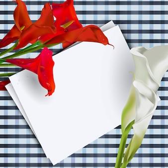 Composizione di fiori di calla con un foglio di testo bianco sul tavolo.