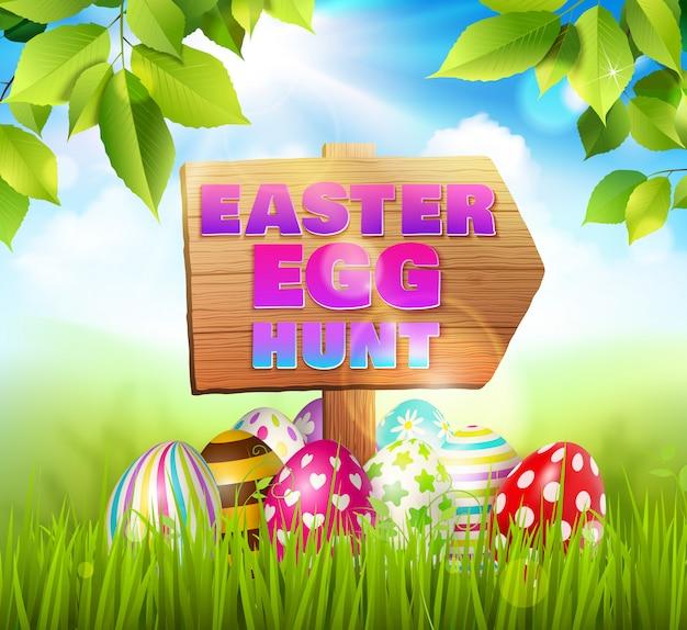 Composizione nel fondo di pasqua con le uova di pasqua che mettono su erba verde e segnale stradale di legno con l'illustrazione del testo