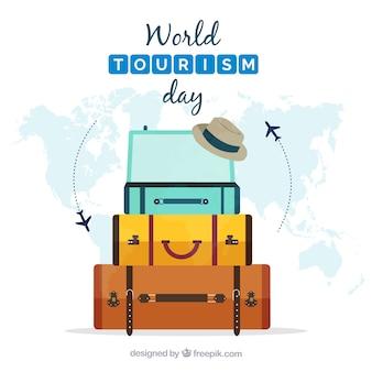 Composizione piatta con bagagli e mappa del mondo