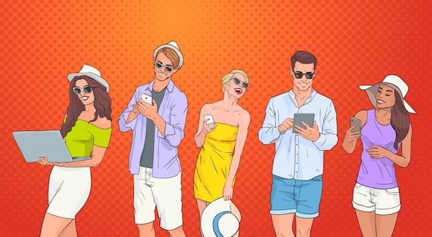 Computer portatile della compressa dello smart phone delle cellule di uso del gruppo della gente che chiacchiera online sopra fondo variopinto di pop art retro
