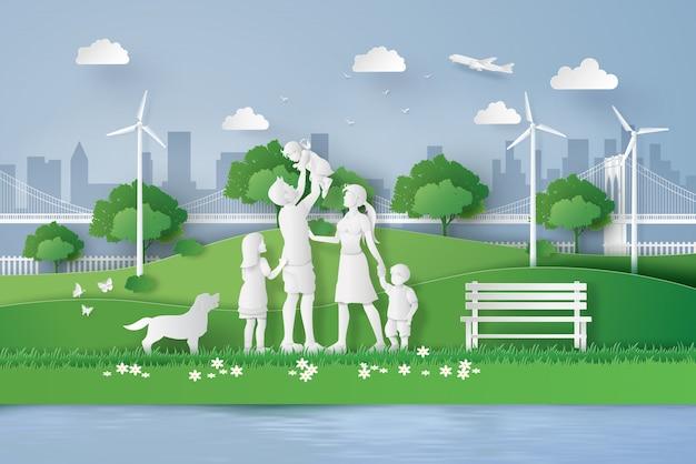 Concetto di eco con la famiglia felice che cammina sul campo