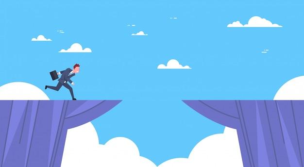 Concetto di rischio e del pericolo d'impresa di jumping over mountain gap dell'uomo d'affari