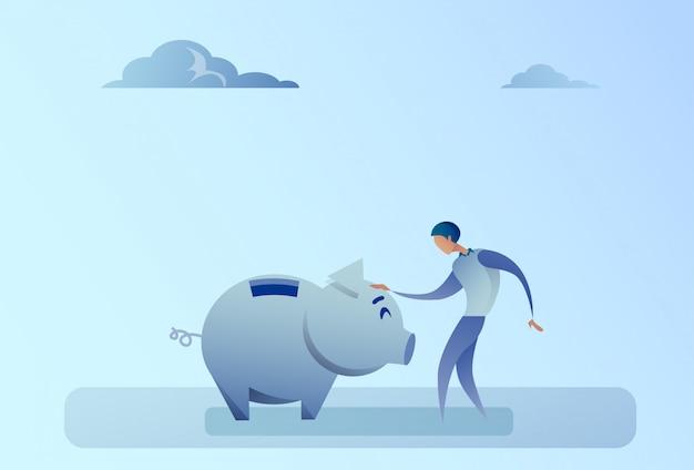 Concetto di risparmio dei soldi del porcellino salvadanaio della tenuta dell'uomo di affari