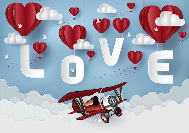 Concetto di san valentino. palloncino rosso che fluttua nel cielo ha la lettera amore ci sono aerei rossi che volano attraverso. stile di arte cartacea