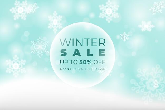 Concetto di vendita inverno sfocato e fiocchi di neve