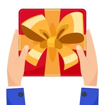 Confezione regalo con fiocco in mano su uno sfondo bianco. la vista dall'alto.