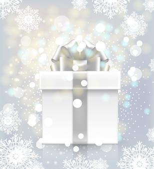 Confezione regalo con fiocco su uno sfondo di fiocchi di neve e luci sfarfallio.