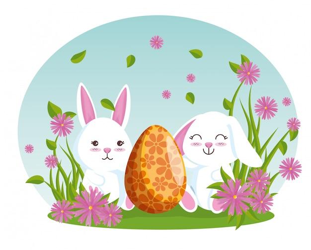 Conigli con mangiatore di uova e piante di fiori