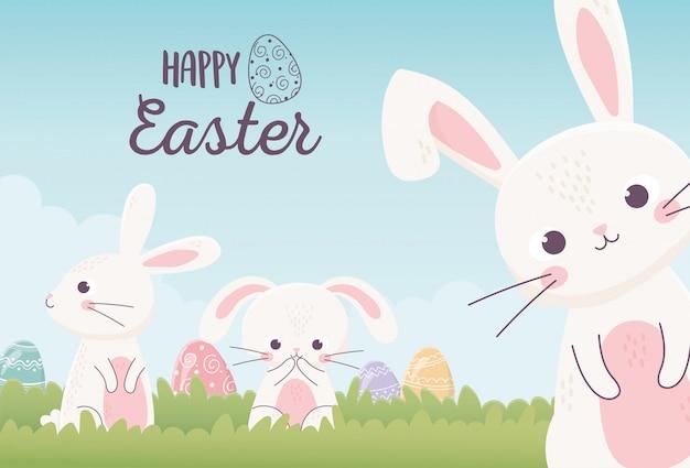 Conigli svegli di pasqua felice con le uova decorative nell'erba, cartolina d'auguri