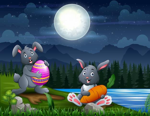 Coniglietti di pasqua felice al paesaggio notturno