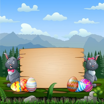 Coniglietti di pasqua felici con le uova di pasqua da un cartello di legno