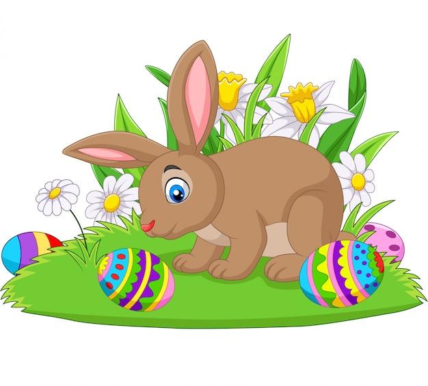 Coniglietto del fumetto con l'uovo di pasqua sull'erba