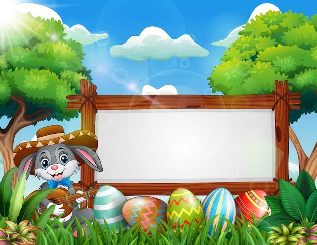Coniglietto di pasqua che gioca chitarra vicino al segno in bianco e all'uovo di pasqua