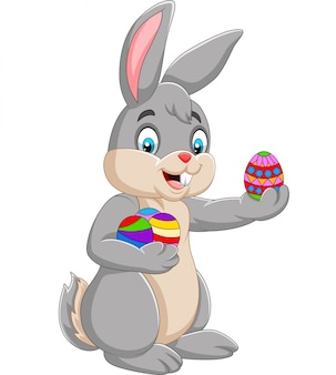 Coniglietto di pasqua che tiene decorato un uovo