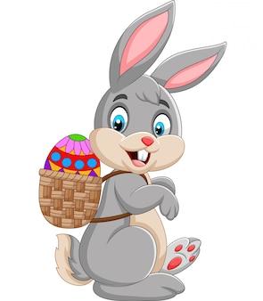 Coniglietto di pasqua che trasporta cestino dell'uovo di pasqua