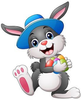 Coniglietto di pasqua felice che porta le uova di trasporto di un cappello