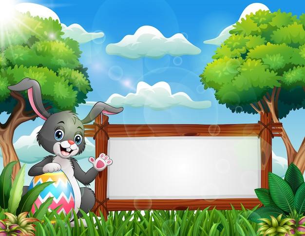 Coniglietto di pasqua in possesso di un grande uovo vicino a un segno in bianco