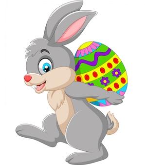 Coniglio cartone animato che trasportano un uovo di pasqua
