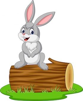 Coniglio cartone animato seduto su un tronco