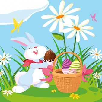Coniglio con le uova di pasqua con il cestino in giardino
