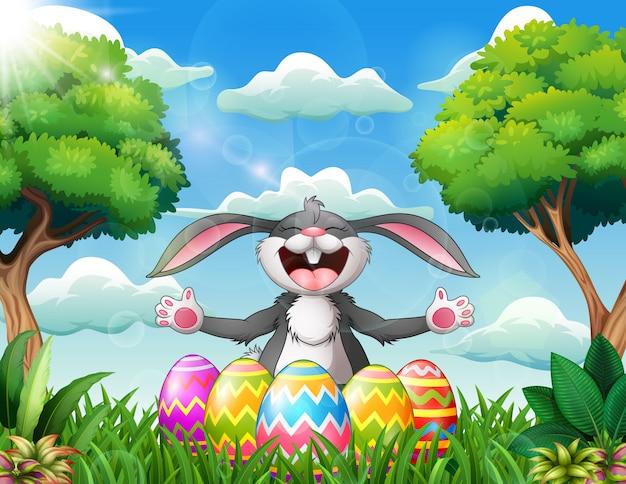 Coniglio del fumetto che ride con cinque uova di pasqua decorate
