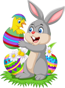 Coniglio del fumetto che tiene un pulcino del bambino che cova da un uovo di pasqua