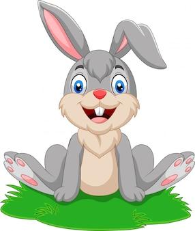 Coniglio divertente del fumetto che si siede sull'erba