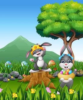 Coniglio felice che tiene l'uovo di pasqua sul campo