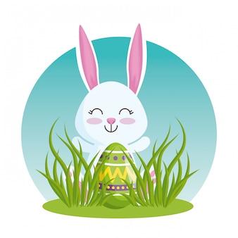Coniglio felice con l'uovo di pasqua nell'erba