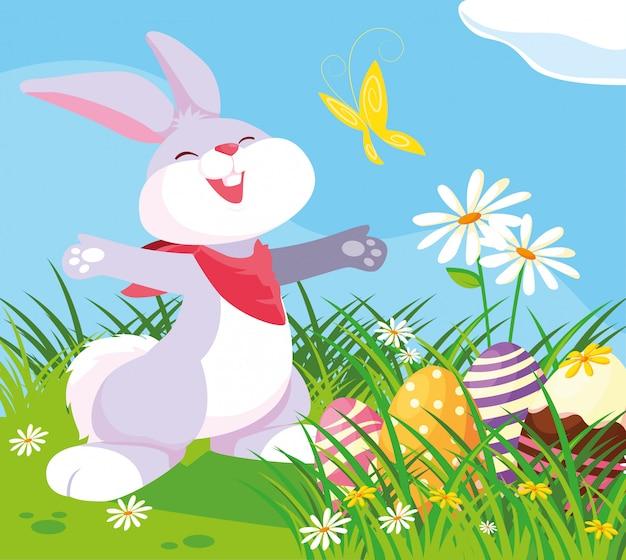 Coniglio sveglio con le uova di pasqua in giardino