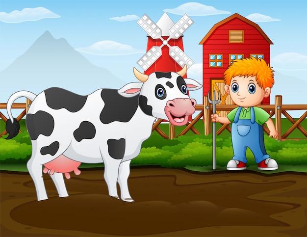 Contadino con una mucca di fronte al suo fienile