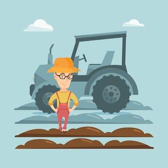 Contadino in piedi con il trattore