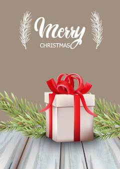 Contenitore di regalo di buon natale con nastro rosso e foglie di abete