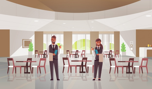 Coppia di camerieri professionisti in piedi insieme