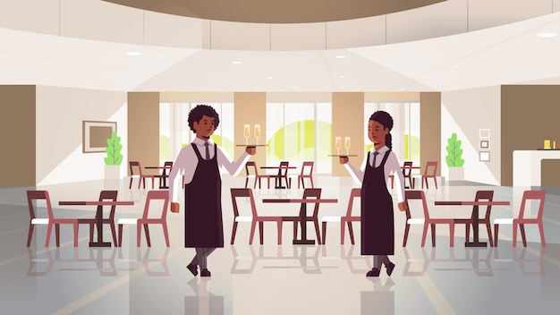 Coppia di camerieri tenendo il vassoio da portata con due bicchieri di champagne