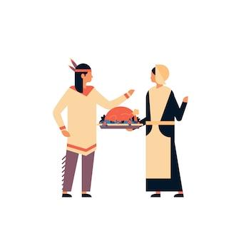 Coppia di indiani nativi americani che celebra la bandiera del giorno del ringraziamento