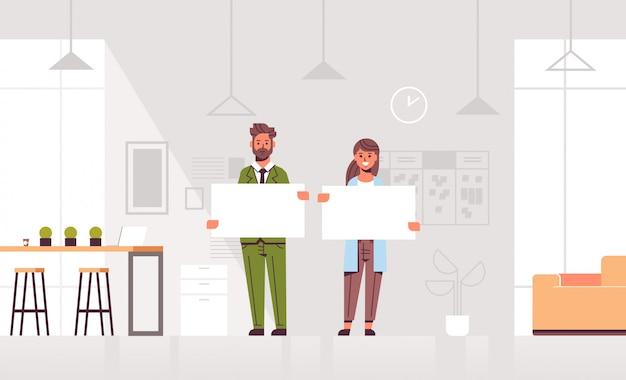 Coppia di uomini d'affari che tiene cartello bianco vuoto business man donna partner mostrando interno bianco ufficio moderno annuncio di cartone bianco vuoto