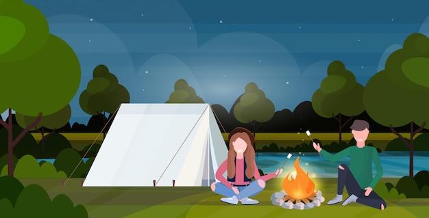 Coppia escursionisti torrefazione caramelle marshmallow sul fuoco escursionismo campeggio concetto uomo donna viaggiatori su escursione notte paesaggio natura sfondo orizzontale a piena lunghezza piatta