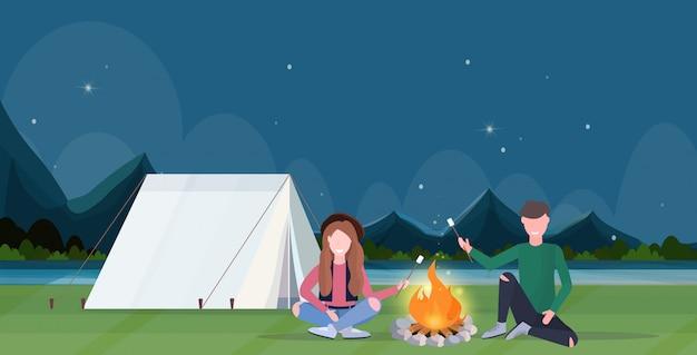 Coppia escursionisti torrefazione caramelle marshmallow sul fuoco escursionismo campeggio concetto uomo donne viaggiatori su escursione notte montagne paesaggio natura sfondo orizzontale a piena lunghezza piatta