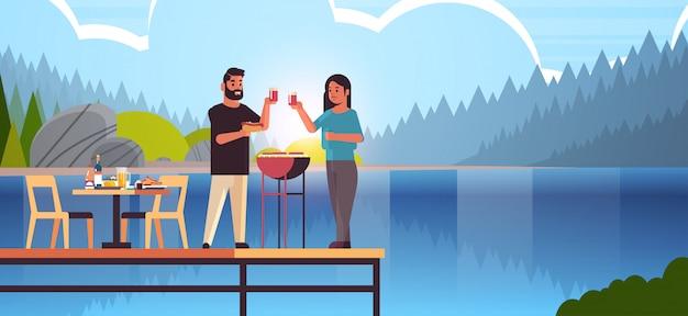 Coppia felice preparazione hot dog sulla griglia e bere vino uomo donna innamorata in piedi sul molo di legno con pic-nic concetto di riva del fiume paesaggio sfondo a figura intera orizzontale