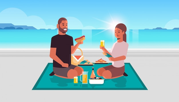Coppia felice, seduta, coperta, mangiare, hot dog, bere, succo, uomo, donna, in, amore, passare, tempo, insieme, a, picnic spiaggia, concetto mare, fondo piatto, lunghezza, orizzontale