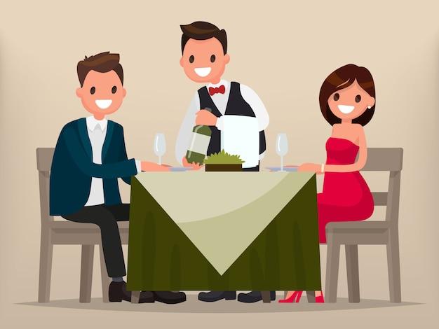 Coppia giovane a cena in un ristorante. uomo e donna seduti a tavola, il cameriere mostra il vino.